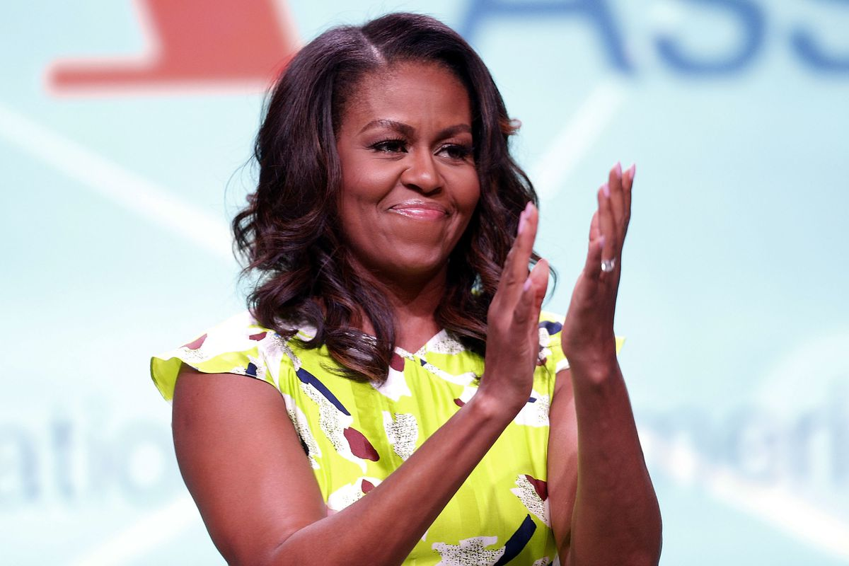 Michelle Obama, wearing a printed green dress, stands onstage, applauding.