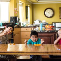 Scott, 14, Hyrum, 6, and Bria, 5, snack on Cheetos after a lunch of noodles, their comfort food. These three children were adopted from China, and Deanne Walker said they have all adapted well into the American culture and their new family.