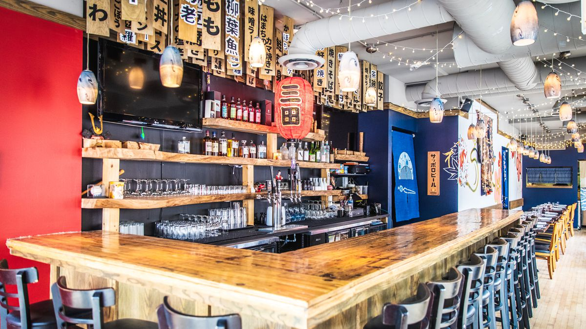 A traditional Japanese-style bar made of polished wood beneath traditional wooden menu blocks with Japanese characters that hang from the ceiling.