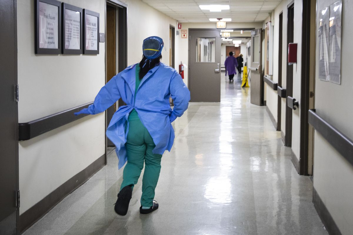 Nurse practitioner Capri Reese runs to respond to a code blue in the intensive care unit at Roseland Community Hospital on April 28. The patient, an 80-year-old man with COVID-19, later died.