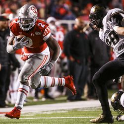 Utah Utes running back Zack Moss (2) runs around the Colorado Buffaloes defensive line during the second half of an NCAA football game at Rice-Eccles Stadium in Salt Lake City on Saturday, Nov. 30, 2019.