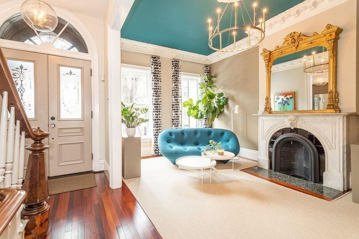 A spacious, airy entry foyer and the sitting room next to it with a fireplace.
