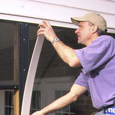 Man Installs Wide Cap Trim For Porched In Screen