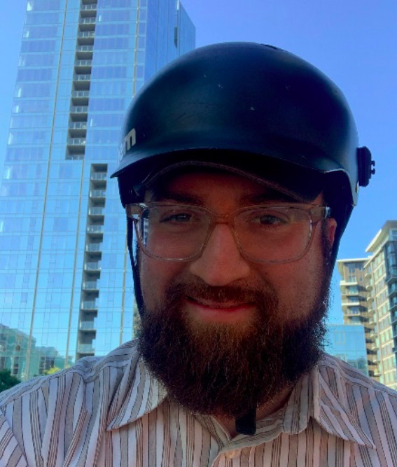 A man with a bushy beard wearing a bike helmet smiles into the camera with tall glass office buildings behind him.