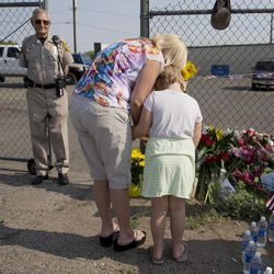Rhonda Chambers says a prayer at a makeshift memorial of flowers and flags with her daughter Ruby Chambers, 6, outside the Granite Mountain Interagency Hot Shot Crew fire station, Monday, July 1, 2013 in Prescott, Ariz. An out-of-control blaze overtook the elite group of firefighters trained to battle the fiercest wildfires, killing 19 members as they tried to protect themselves from the flames under fire-resistant shields. The disaster Sunday afternoon all but wiped out the 20-member Hotshot fire crew leaving the city's fire department reeling. (AP Photo/Julie Jacobson)