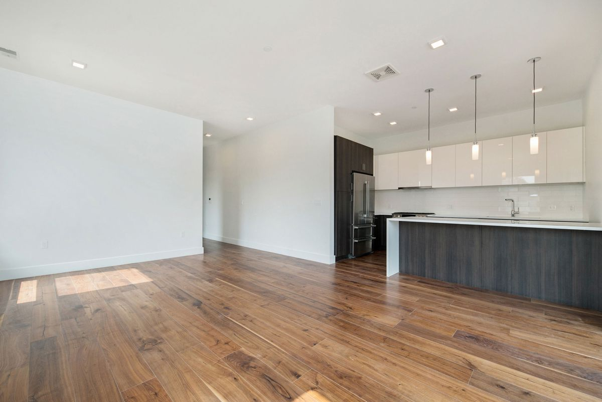 Facing in to the living space and kitchen on shimmering hardwood floors