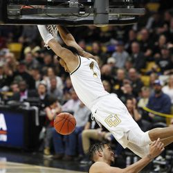Colorado guard Tyler Bey, top, hangs from the rim after dunking over Utah forward Timmy Allen in the second half of an NCAA college basketball game Sunday, Jan. 12, 2020, in Boulder, Colo.