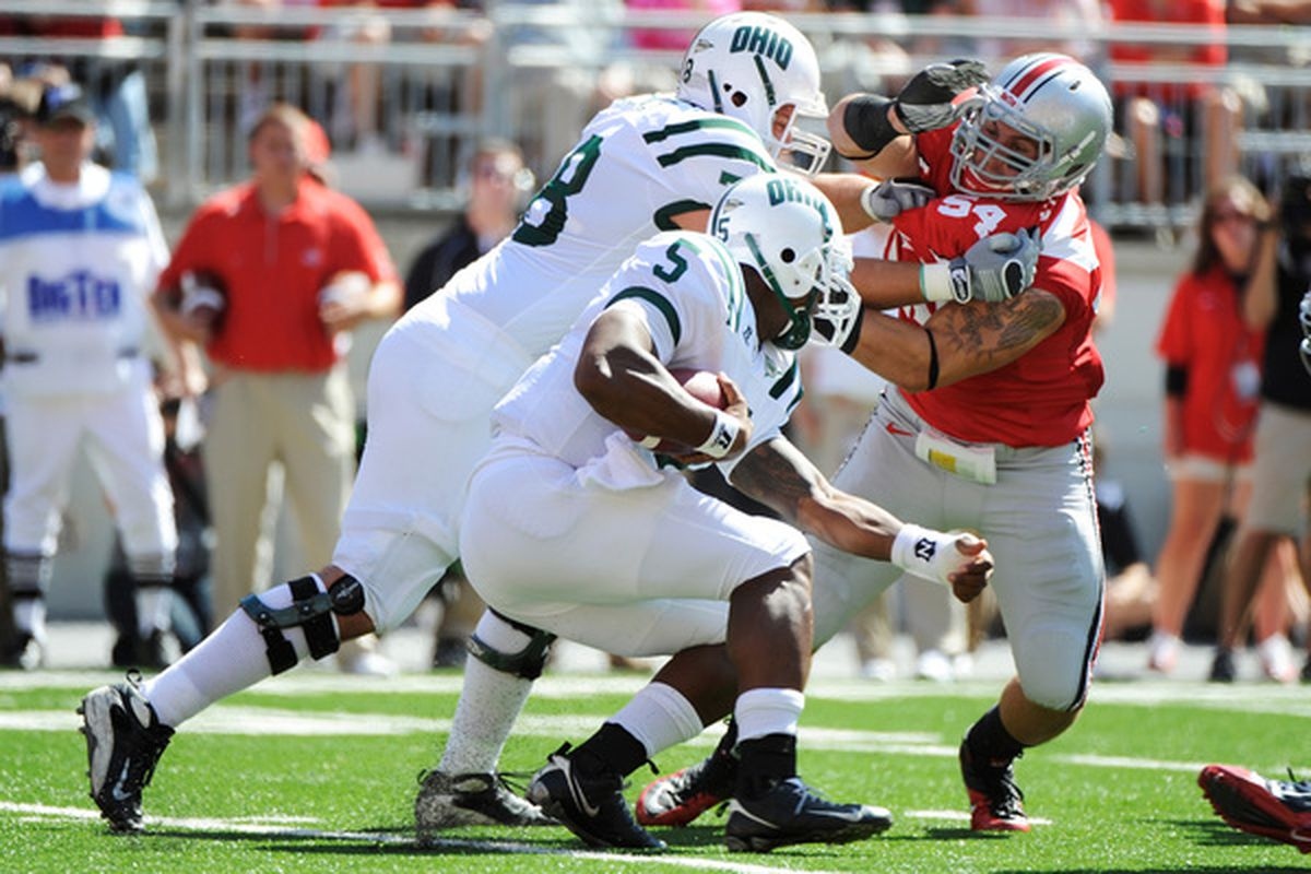 COLUMBUS OH - SEPTEMBER 18:  John Simon #54 of the Ohio State Buckeyes fights off a block to get to ballcarrier Phil Bates #5 of the Ohio Bobcats at Ohio Stadium on September 18 2010 in Columbus Ohio.  (Photo by Jamie Sabau/Getty Images)
