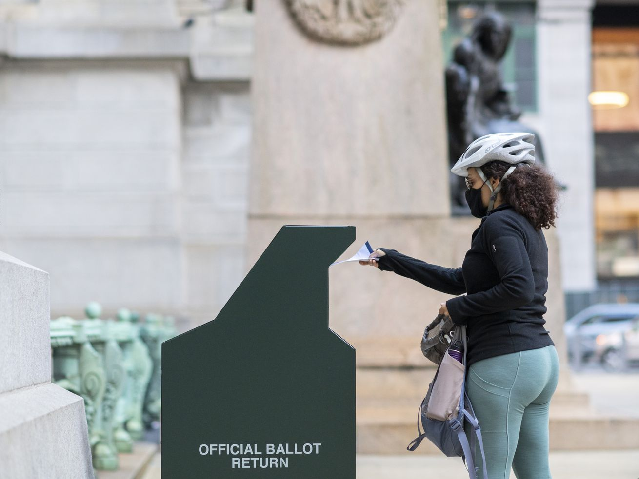 "A woman in a grey bike helmet, black mask, and glasses is seen in profile. She is placing a white envelope into a metal green receptacle that says ""Official Ballot Return"" on the side."