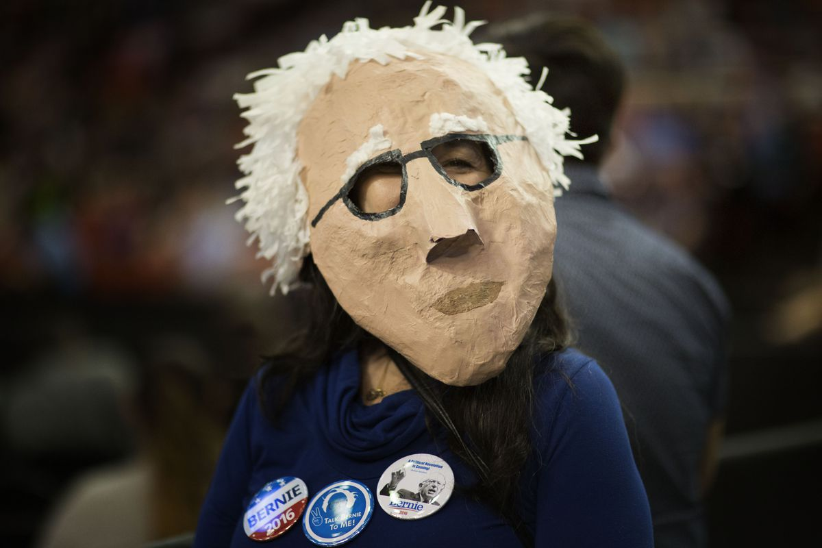 Ellen George wears a mask her sister made during a campaign rally for Democratic Party presidential candidate Bernie Sanders.