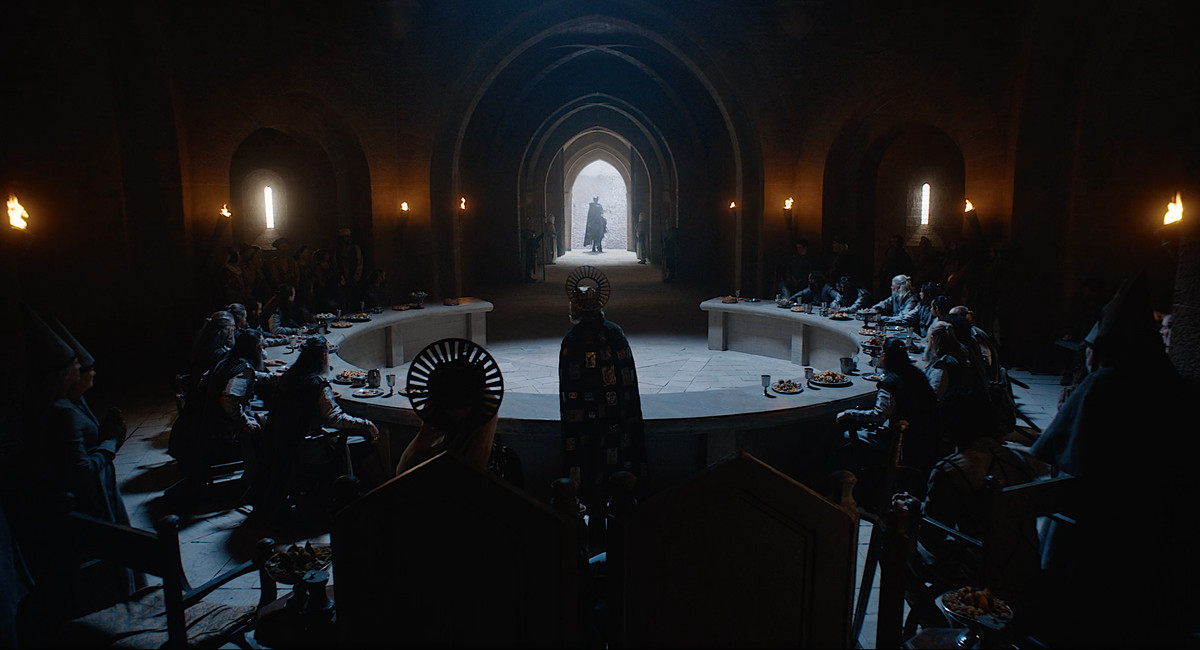 The Green Knight stands silhouetted in the doorway of King Arthur's court in David Lowery's The Green Knight