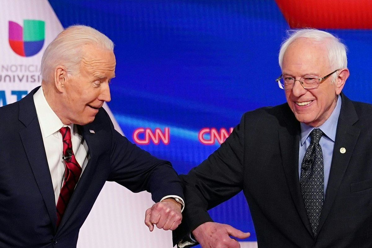 Biden and Sanders smile in suits as they bump elbows.