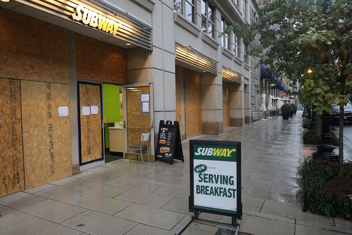 A sign for Subway sandwiches on a sidewalk outside a boarded-up store.
