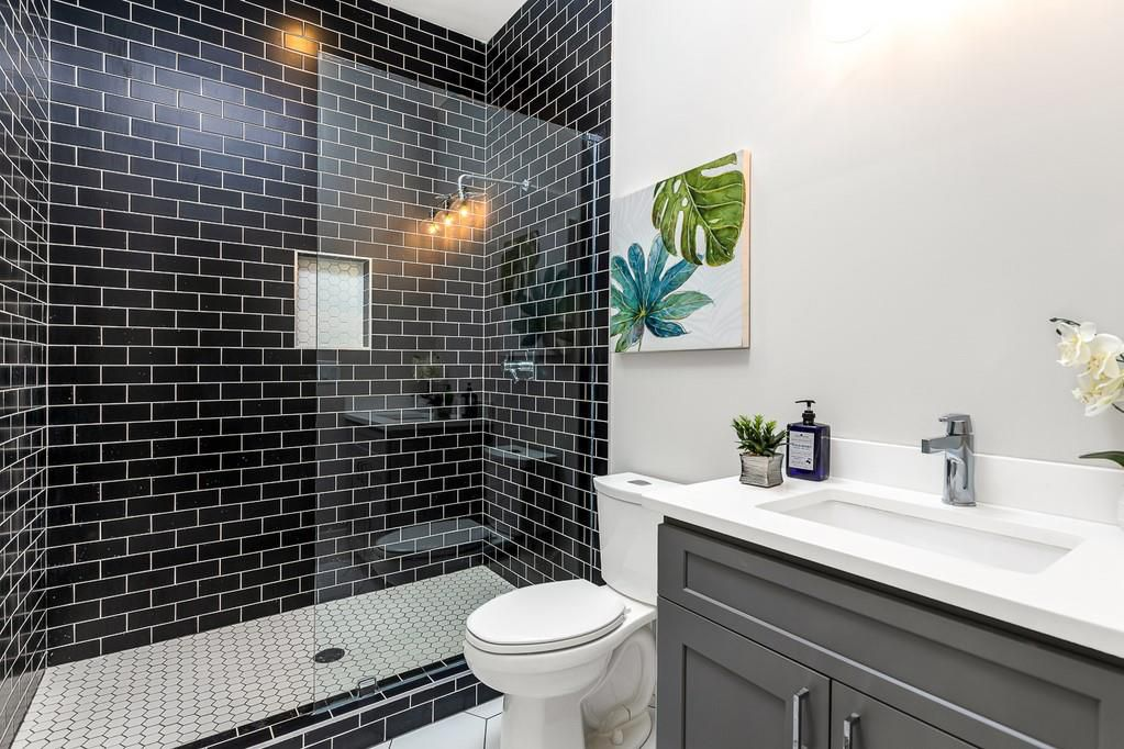 A white bathroom with black tiling around the shower.