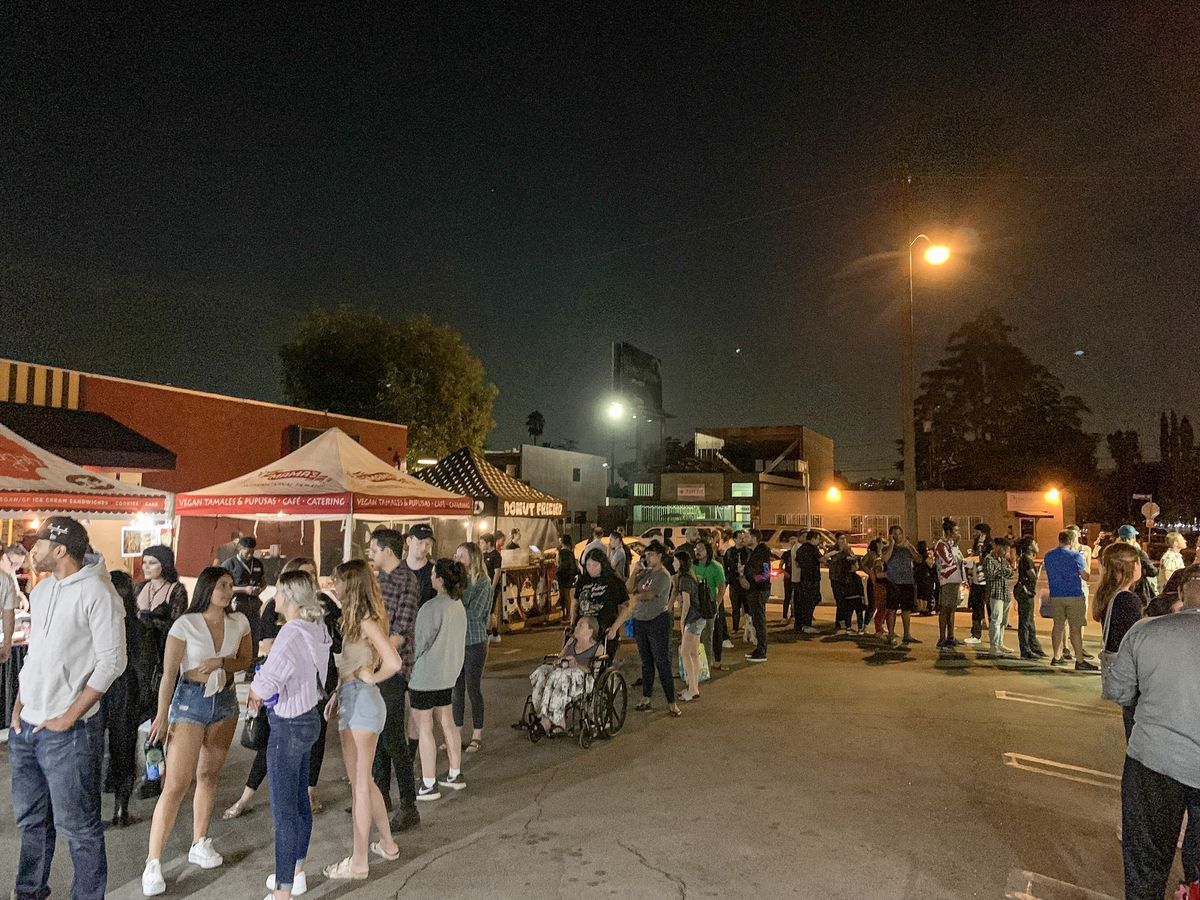 A crowd of vegan diners waits for street food at night in a parking lot.