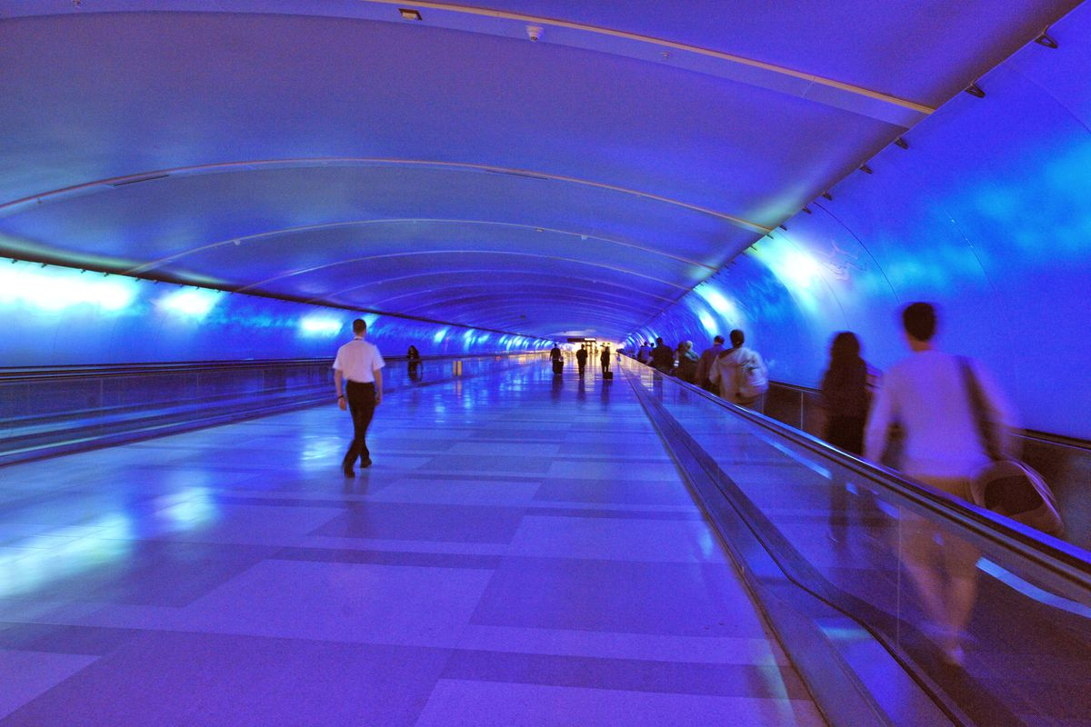 People pass through a tunnel at DTW that's filled with purple light.