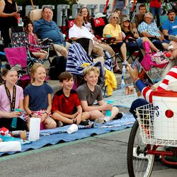 Kids along the Days of '47 Parade route are entertained by a clown in Salt Lake City on Friday, July 23, 2021.