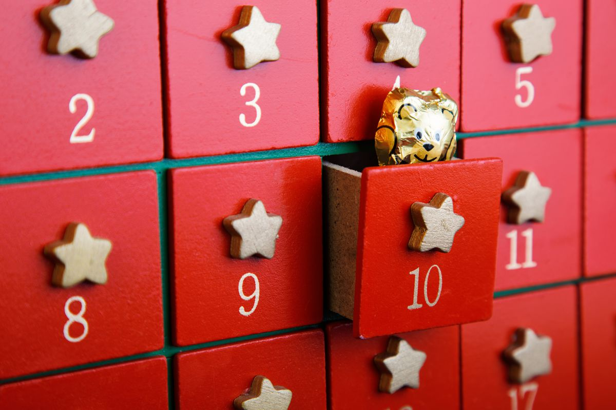 A gold foil-wrapped bear peeks out of the 10th day on an Advent calendar