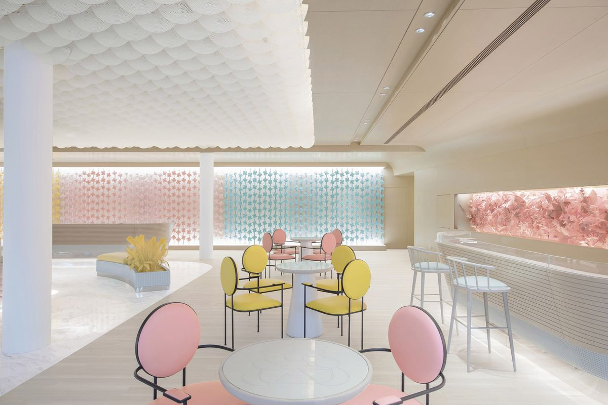 A cafe features pink and yellow chairs against a cream backdrop.