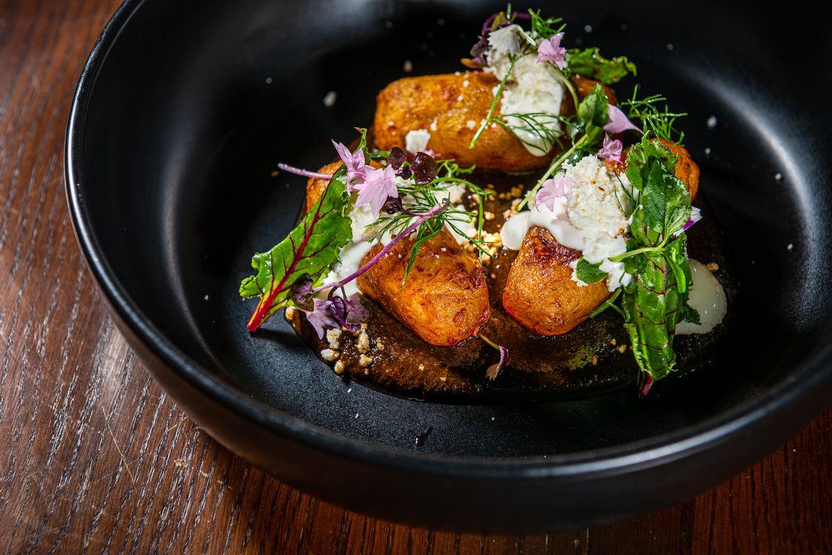 Plantain molotes topped with requeson (fresh cheese) come in a light, acidic chichilo mole