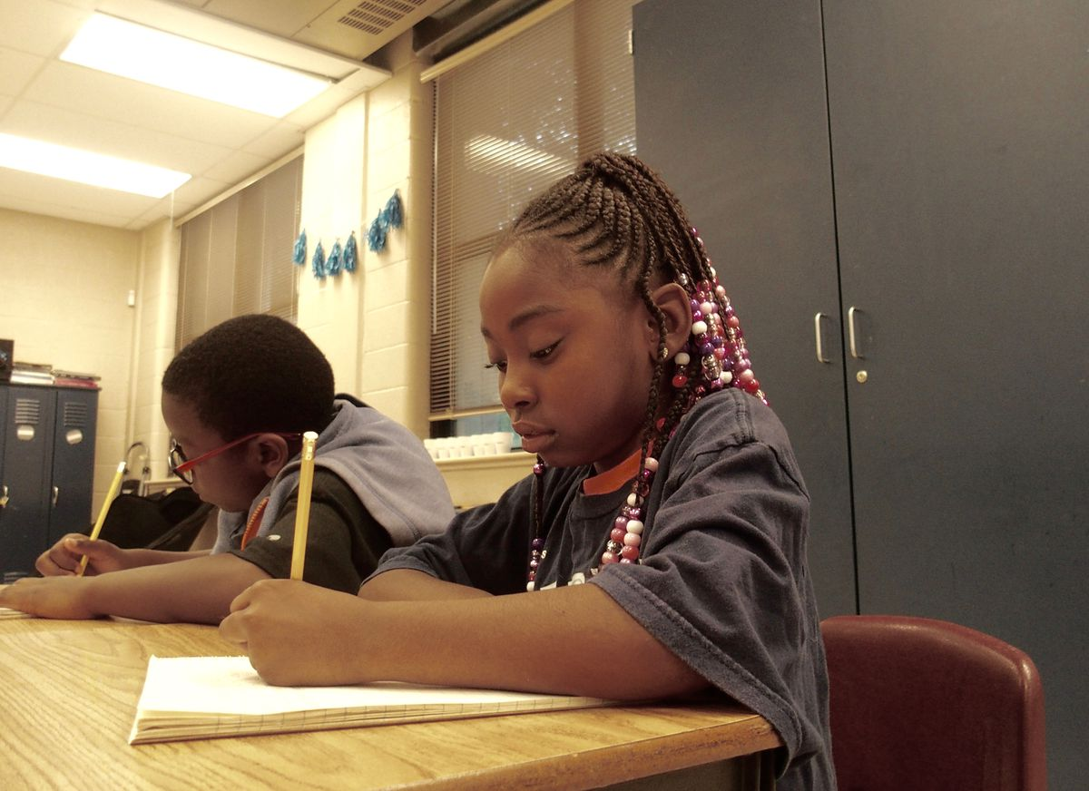 Third-grader Kenyari Harmon, 8, writes a story about her favorite athlete during the Read to be Ready literacy camp held at Cornerstone Prep in Memphis' Frayser neighborhood. June 27, 2019.