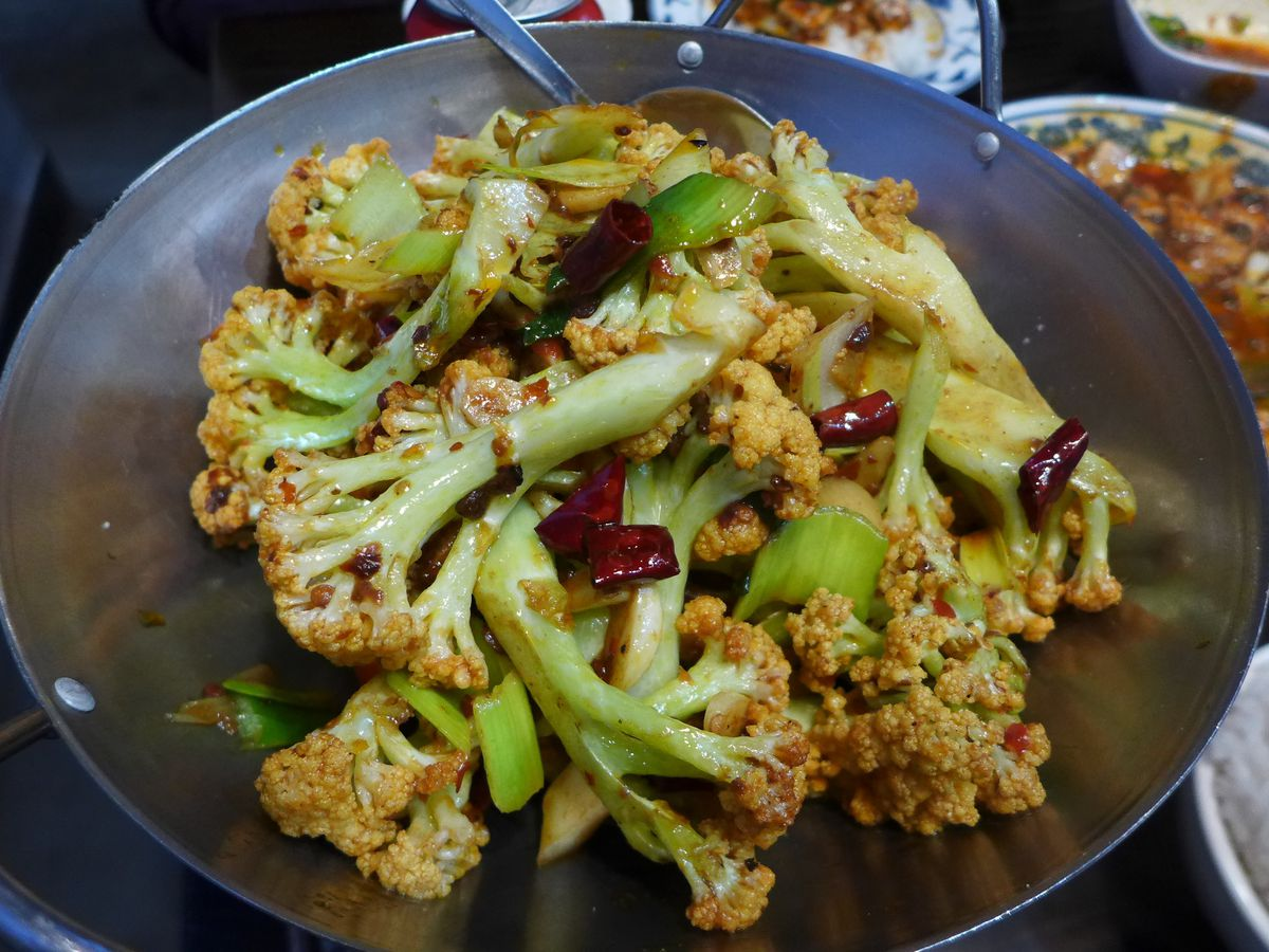 A dish of green stemmed cauliflower in a wok with ma po tofu brown and red in a background bowl.