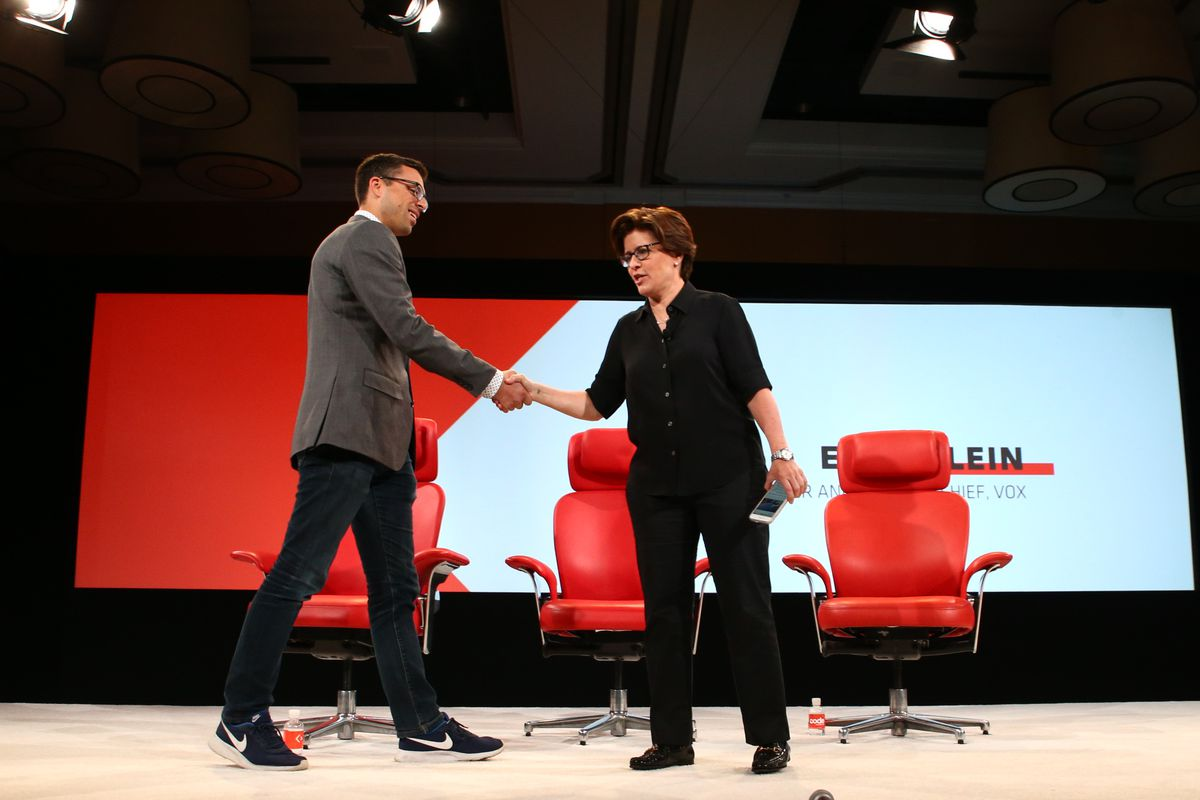 Recode founder Kara Swisher and Vox.com founder Ezra Klein shaking hands onstage at the 2016 Code Conference