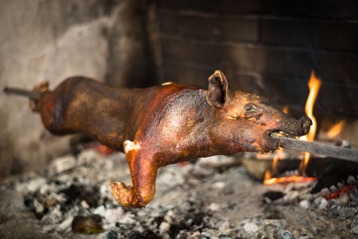 A suckling pig rotates on a spit over a live fire