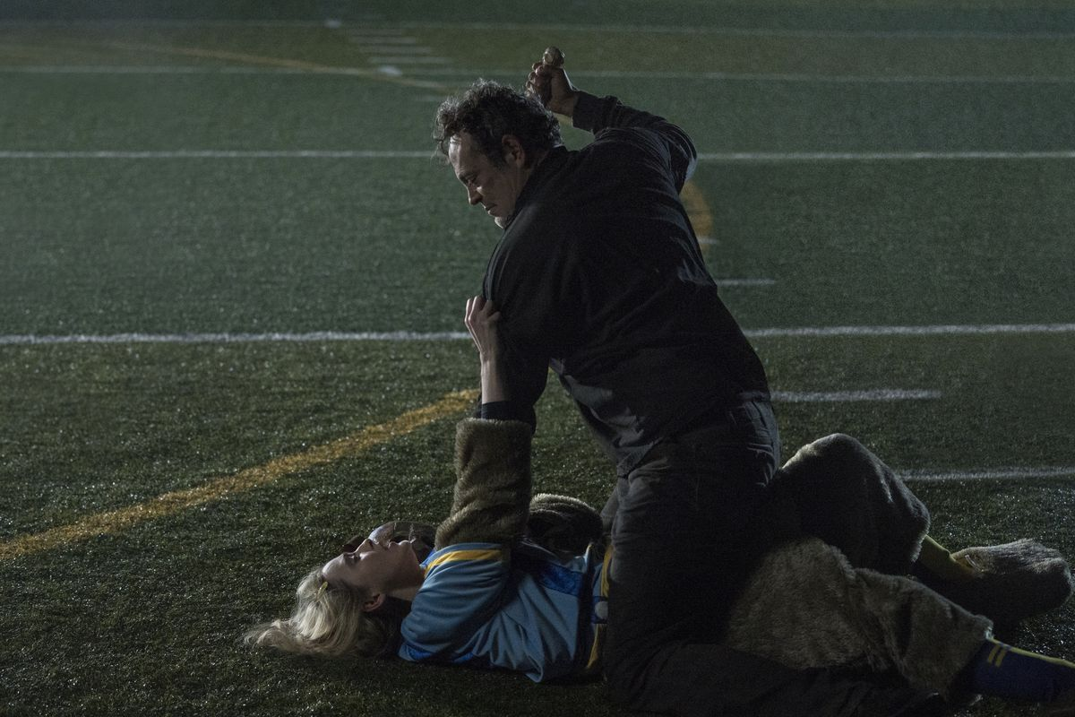 Vince Vaughn straddles Kathryn Newton at night on a football field as he attempts to stab her in Freaky