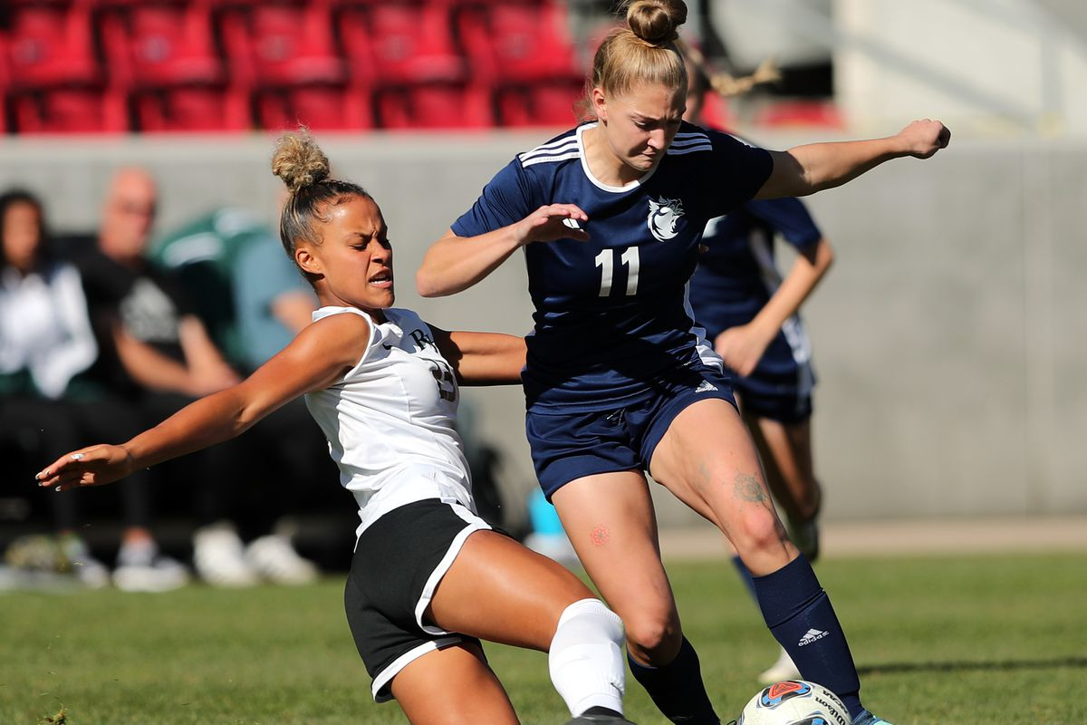 Rowland Hall's Jordan Crockett kicks the ball away from Real Salt Lake Academy's Natalie Scott as they play in the 2A state soccer championship at Rio Tinto Stadium in Sandy on Saturday, Oct. 26, 2019. Rowland Hall won in a shootout after two overtime periods.