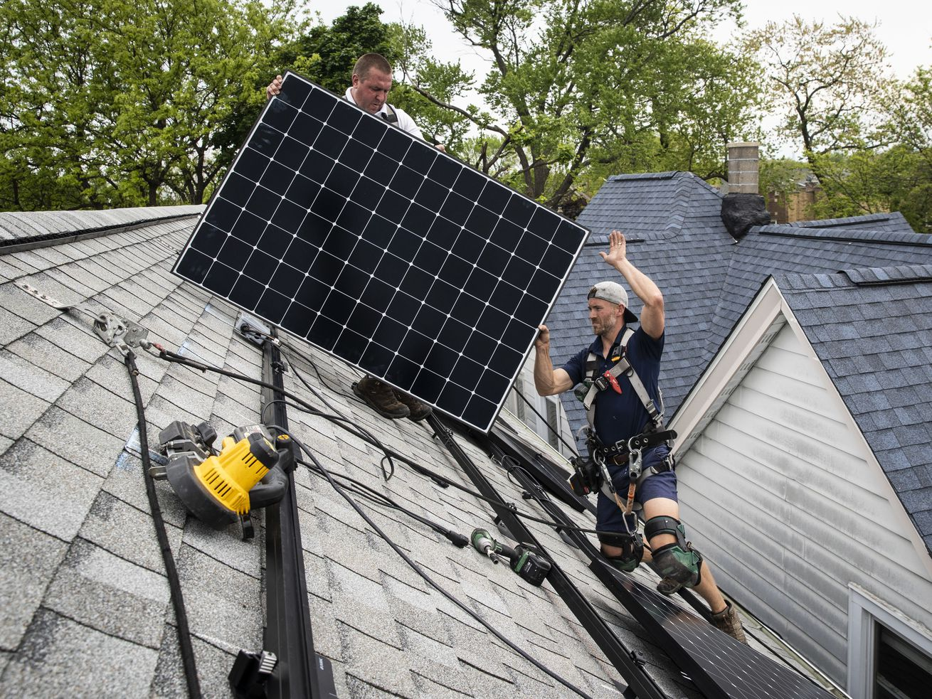 Pete Southerton (left) and Tom Bradshaw install solar panels on a Northwest Side home. Their employer, Certasun, and other companies have had to lay off workers as money promised by a 2016 Illinois law dried up.