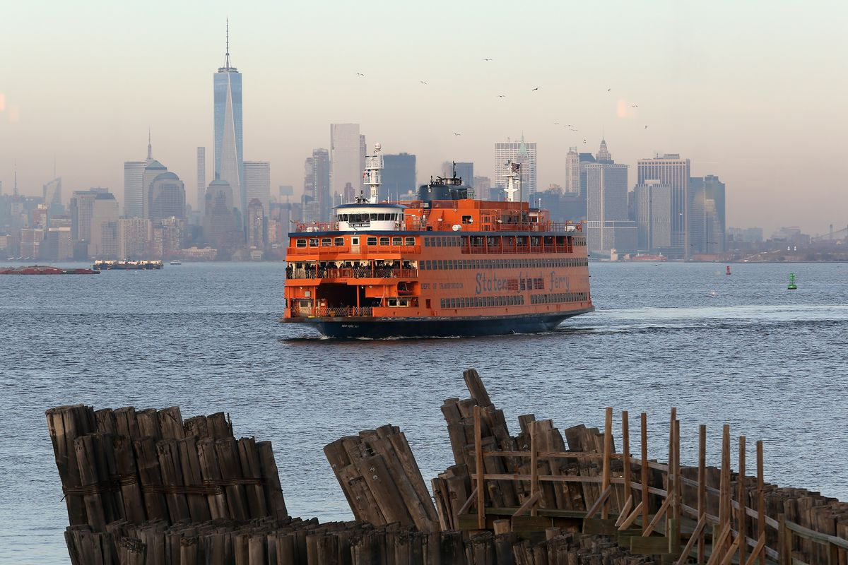 A ferry arrives at Staten Island, with the Manhattan skyline behind it.