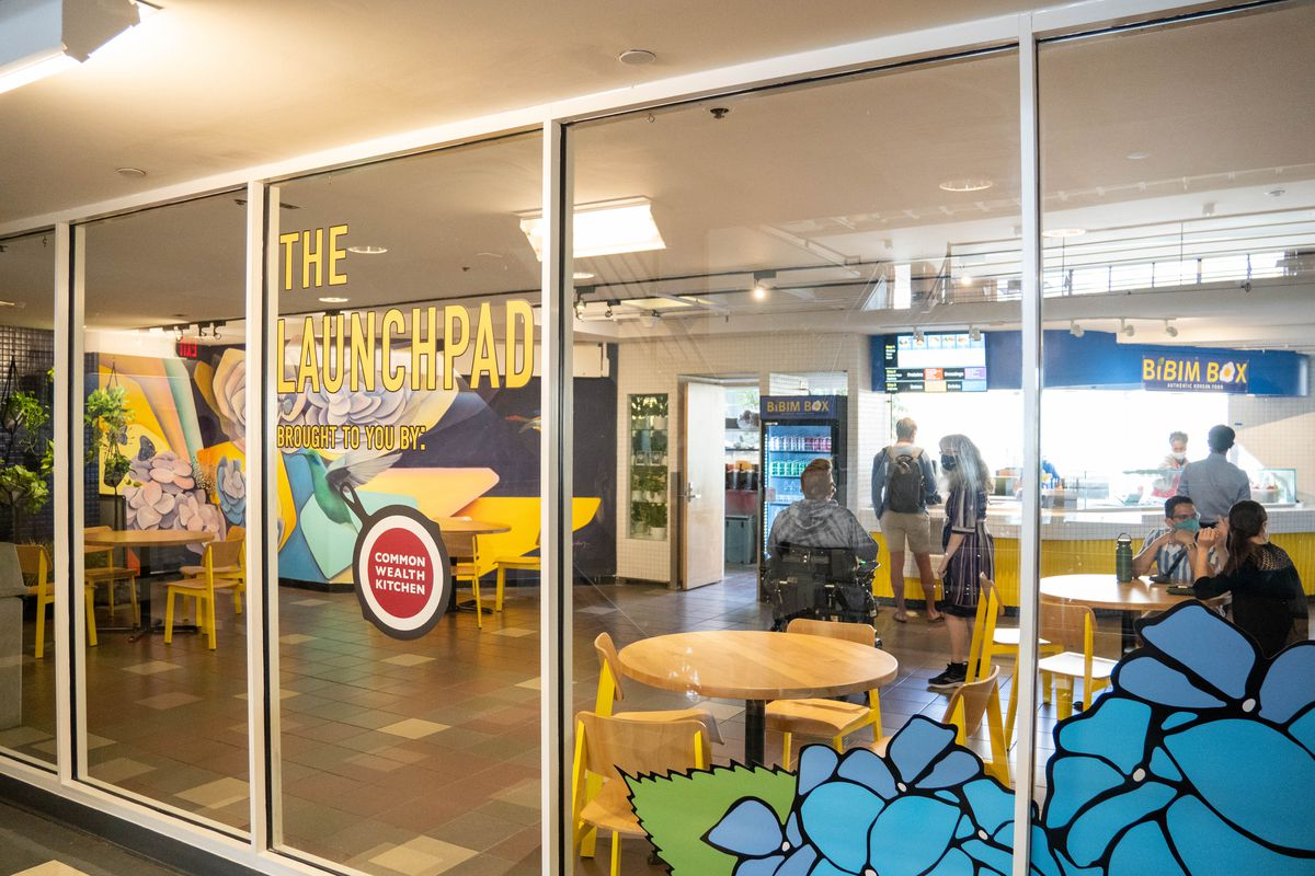 """Floor to ceiling glass walls with text graphics that read """"The Launchpad"""" and """"Commonwealth Kitchen"""" pasted on the front. Behind the glass there is a food court."""