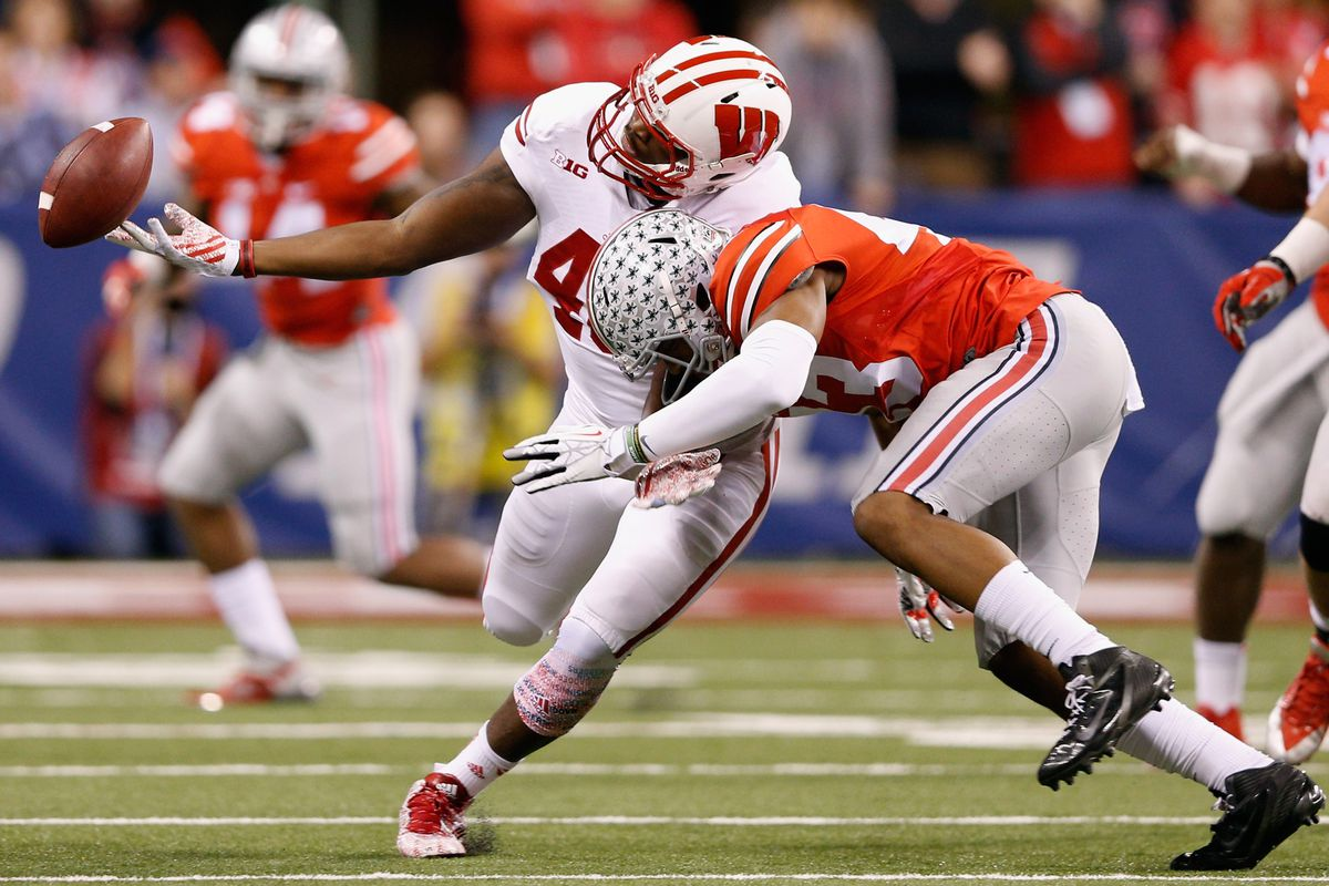 INDIANAPOLIS, IN - DECEMBER 06:  Sam Arneson #49 of the Wisconsin Badgers loses the ball next to Darron Lee #43 of the Ohio State Buckeyes during the Big Ten Championship at Lucas Oil Stadium on December 6, 2014 in Indianapolis, Indiana. The Buckeyes won the game 59-0. (Photo by Joe Robbins/Getty Images)
