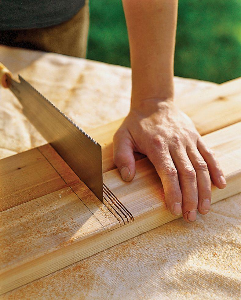 Man Uses Handsaw To Make Kerf Cuts On Trellis Frame