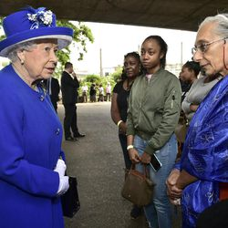 Britain's Queen Elizabeth II, left, meets members of the community affected by the fire at Grenfell Tower in west London during a visit to the Westway Sports Centre which is providing temporary shelter for those who have been made homeless in the disaster, Friday June 16, 2017. Relatives of those missing after a high-rise tower blaze in London are searching frantically for their loved ones, as the police commander in charge of the investigation says he hopes the death toll will not rise to three figures.