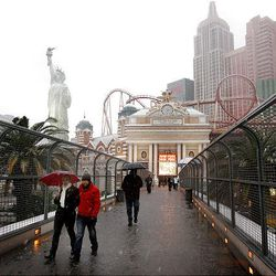 People cross the street in the snow on a sky-bridge Wednesday with the New York New York hotel and casino in the background.