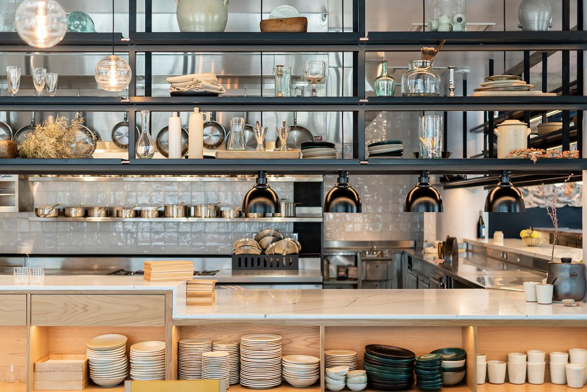 An open kitchen at a hot new restaurant, complete with pots and pans.
