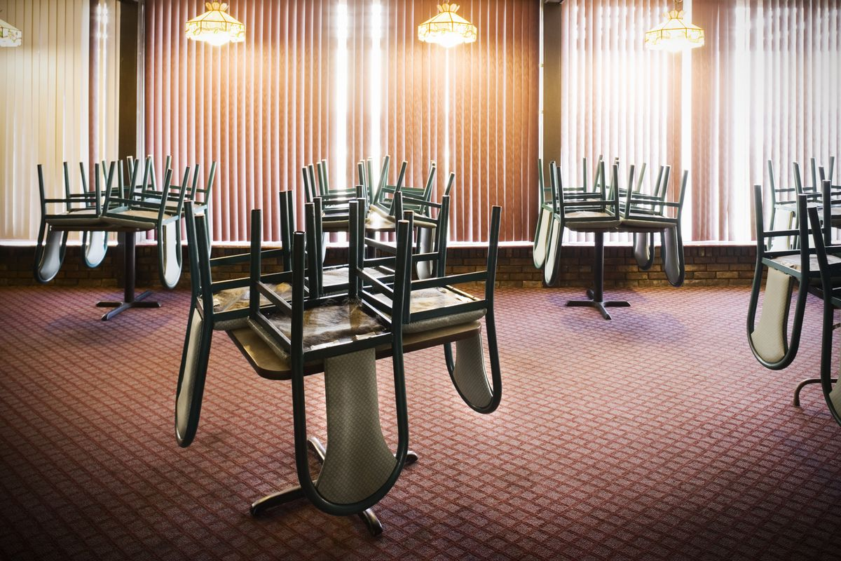 A photo of an empty restaurant dining room with chairs stacked on the tables