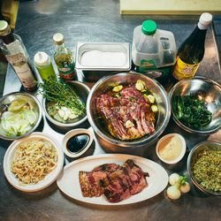 <b>The Ingredients</b>.  Top row, left to right: Red wine vinegar, olive oil, pomegranate molasses, salt, low sodium soy sauce, and rice wine vinegar. <br> Center Row, left to right: Green onion bulbs, thyme, garlic, skirt steak in marinade, and grilled