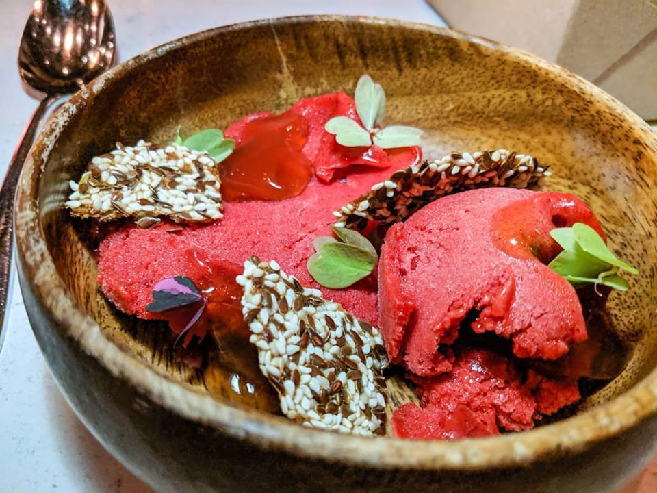 Several scoops of bright red sorbet are served in a wooden bowl with delicate greens and seeded crackers