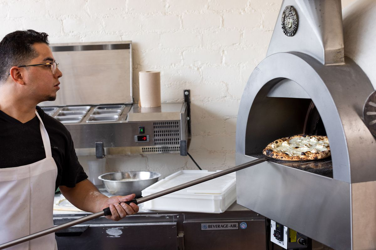 A pizza chef holds a pizza that has just come out of a wood-fired oven.