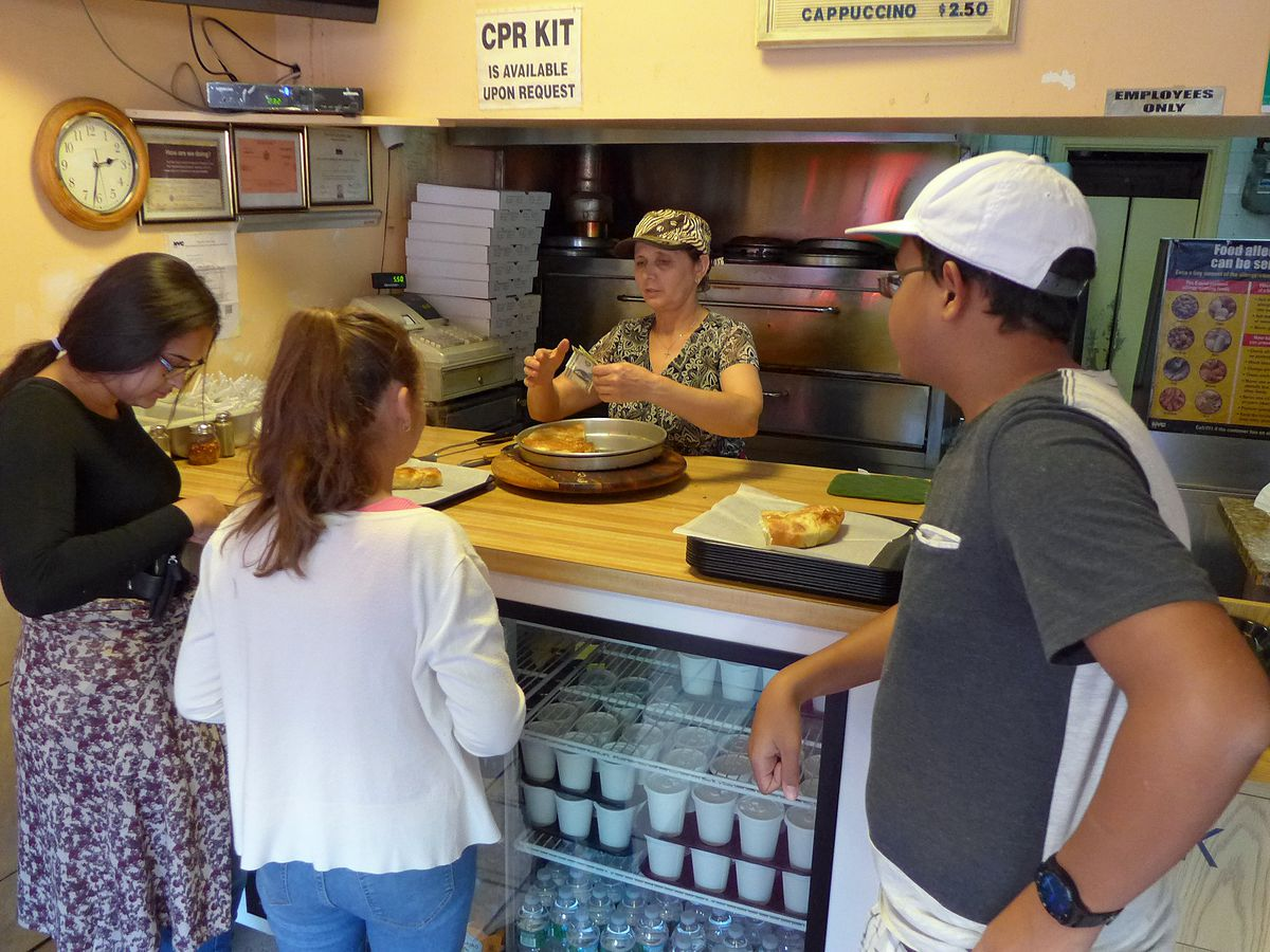 A group stand around a couter, behind which a woman in a baseball cap sells filo pies.