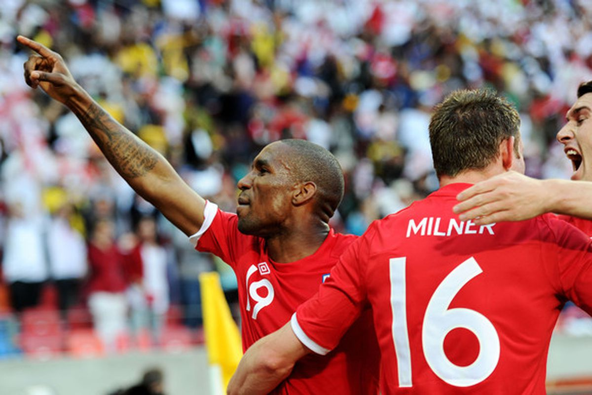 PORT ELIZABETH, SOUTH AFRICA - JUNE 23:  Jermain Defoe celebrates with James Milner after scoring against Algeria, while Gareth Barry looks poised to bite James on the neck to complete his transformation. (Photo by Laurence Griffiths/Getty Images)