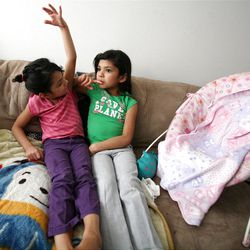 Juliza and Ariza Carreon watch television at home in Taylorsville on Saturday, Feb. 9, 2013. Carreron's family was recently evicted, but they managed to land on their feet.