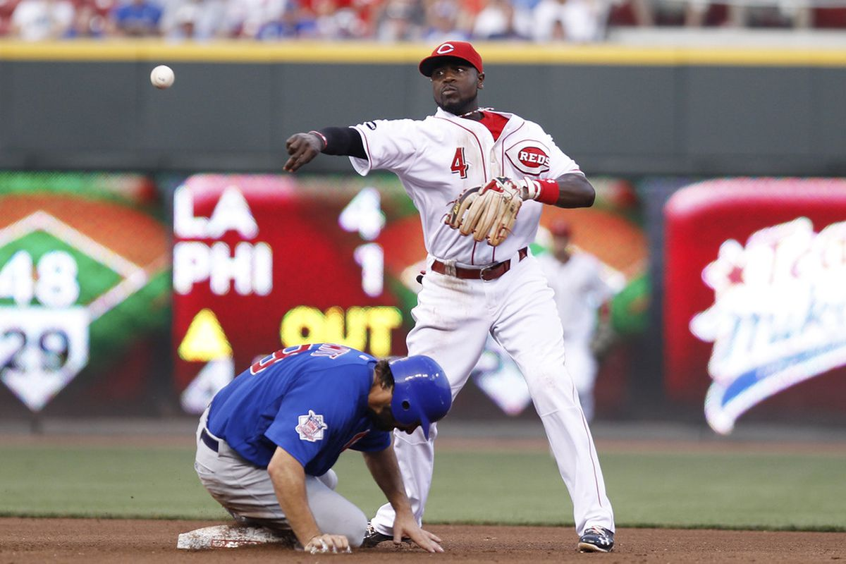 Brandon Phillips of the Cincinnati Reds throws to first to turn a double play over Blake DeWitt of the Chicago Cubs at Great American Ball Park on June 7, 2011 in Cincinnati, Ohio. (Photo by Joe Robbins/Getty Images)