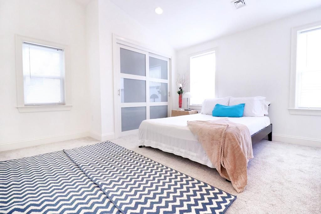 A spacious bedroom with a large bed and there's rug splayed in front of it,