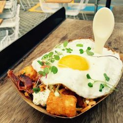 Crisp Tots & Local Egg (chili butter, cheddar cheese, herbed goat cheese, avocado crema sauce, bacon, micro greens)