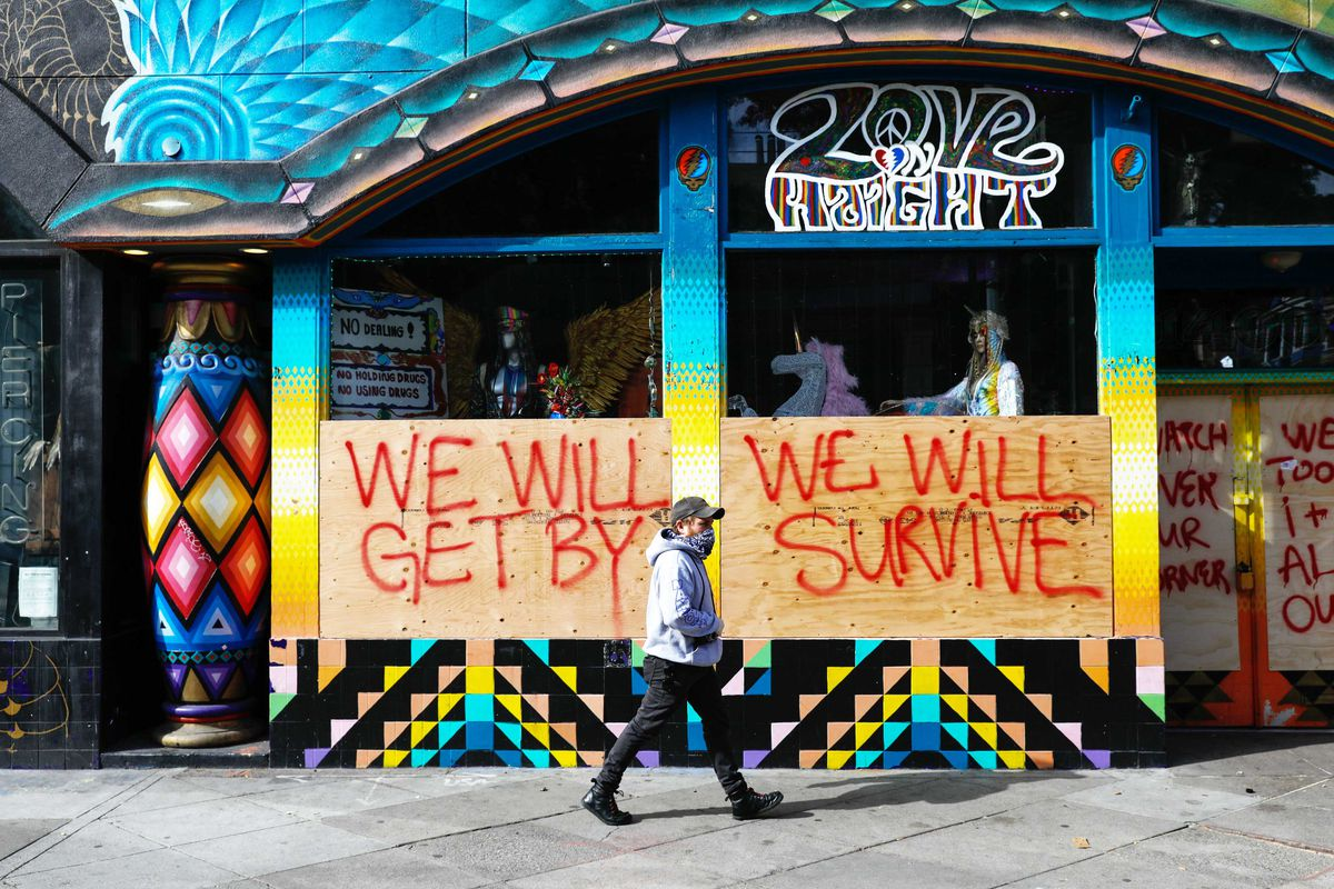 """A man in a mask passes by a boarded up store that has """"we will get by we will survive"""" written on the boards."""