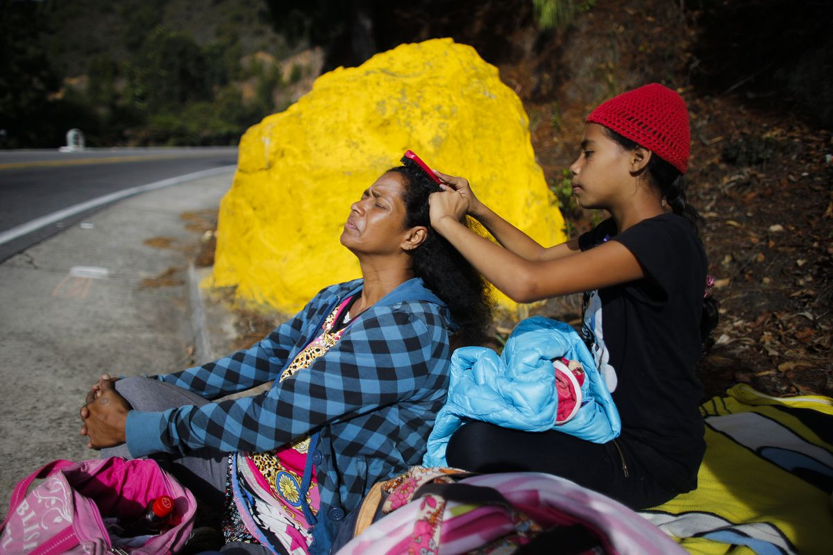 September 1:  Angelis Cadiz, 10, combs her mother Sandra's hair, as they take a break from walking from Venezuela to Peru. The daughter of a housewife and a cemetery worker, Sandra had grown up to know great misfortune, but she had never expected to know